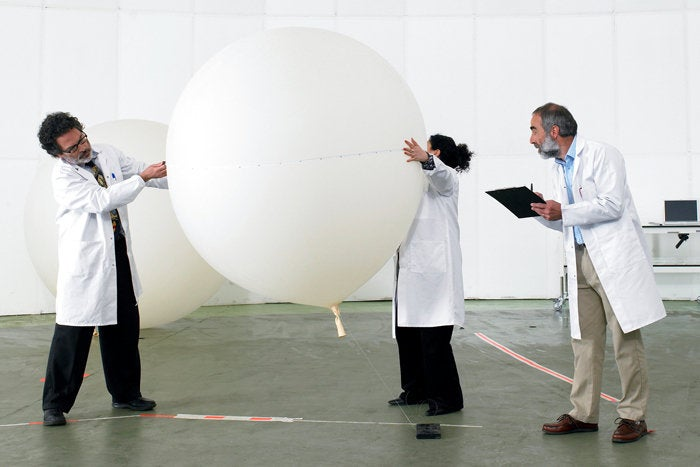 3 people in lab coats testing balloon QA