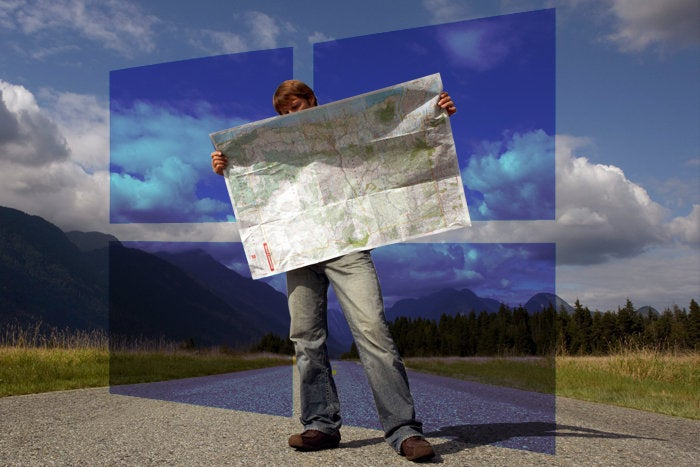 man holding map with windows 10 logo in background