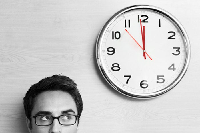 Man looking up at clock on wall deadline