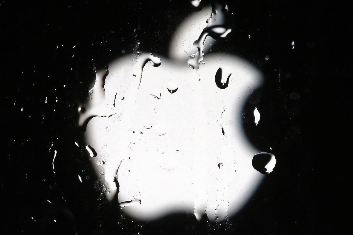 Abstract Apple logo behind rainy glass