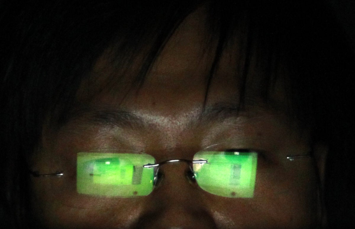 Hacker with computer reflecting off of glasses
