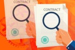 hand holding magnifying glass over contract