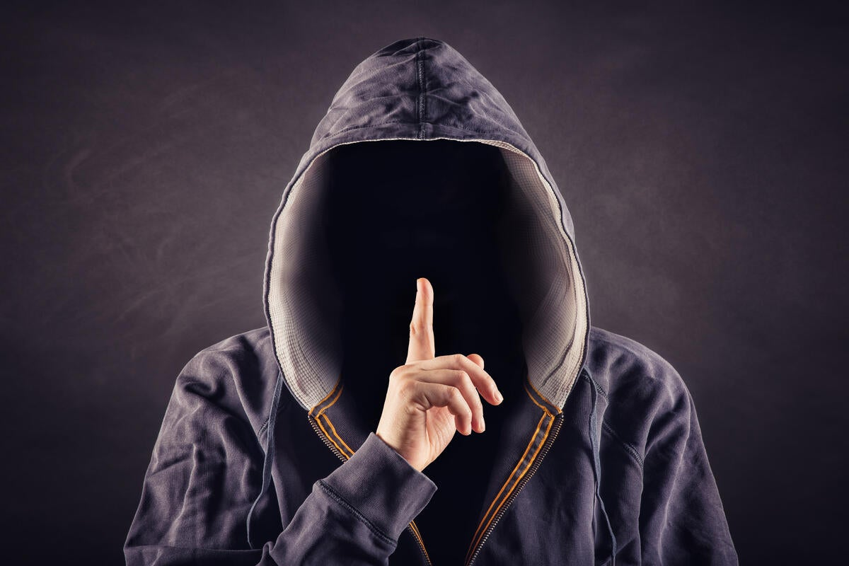 Hacker in hoodie holding up finger to be quiet secret