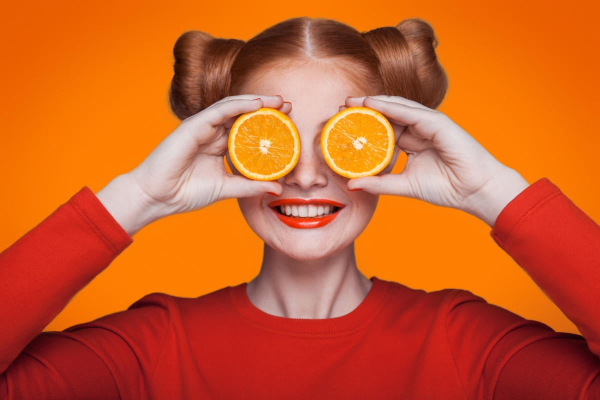 Fun girl with red lipstick holding orange slices over her eyes