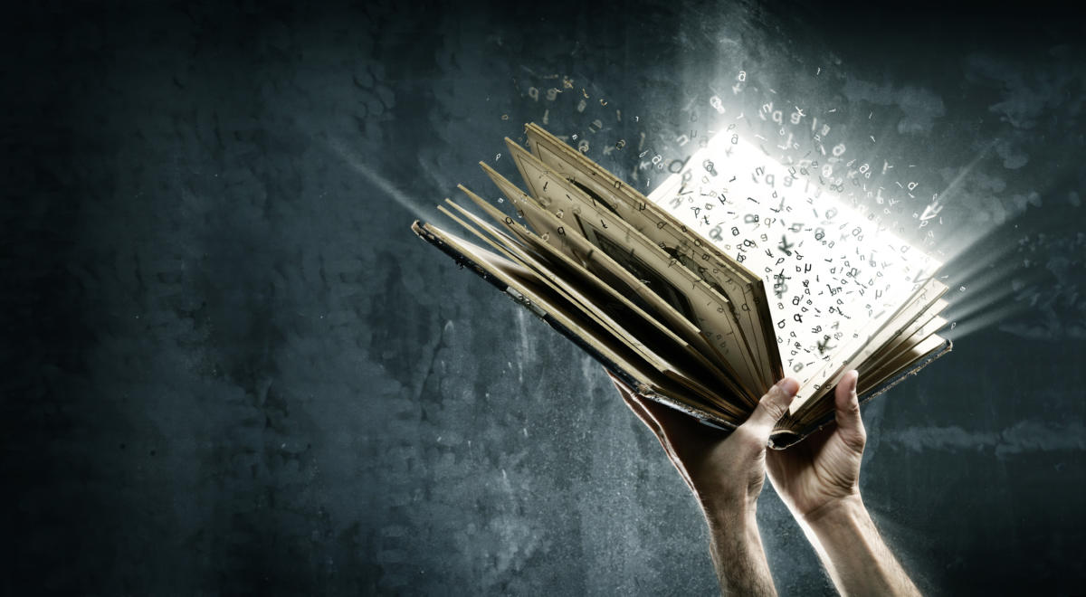 Hands holding book with exploding words