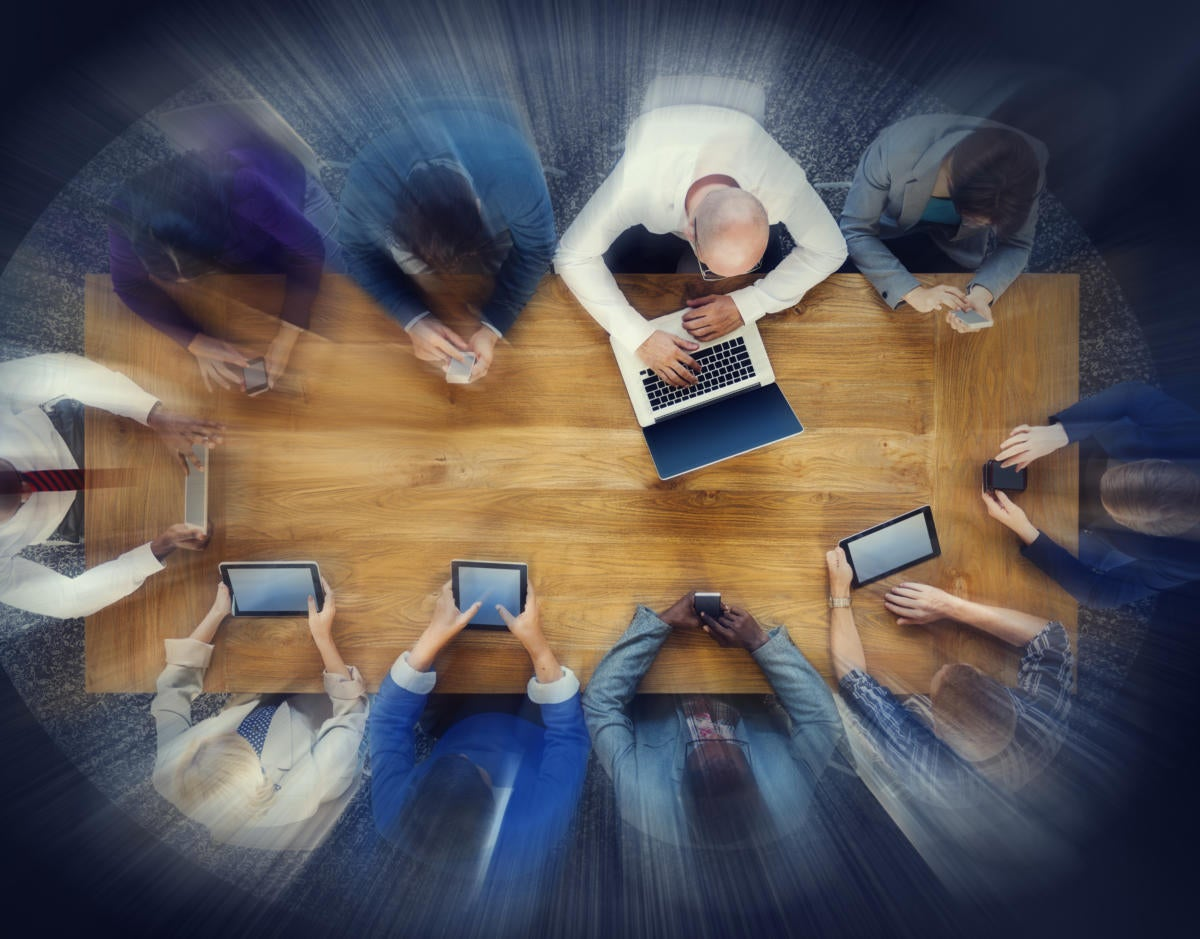 Group of workers collaborating around a table with mobile devices
