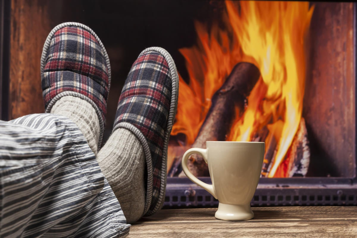 person with slippers sitting on couch with fire in background