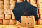 Parcels and stacked packages being protected by black umbrella