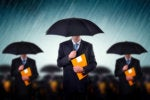 businessmen with umbrellas risk protected storm