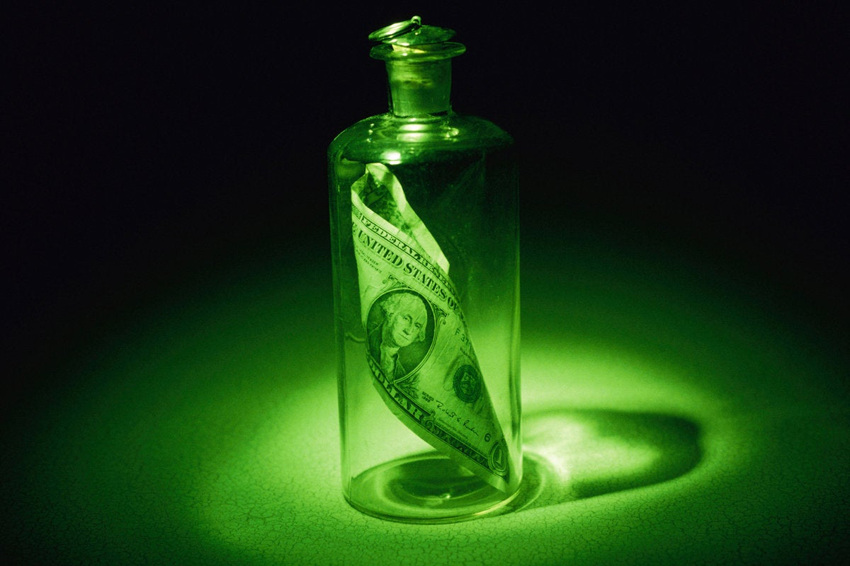 green bottle with money inside save message in a bottle