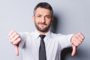 man holding thumbs down dislike disapprove