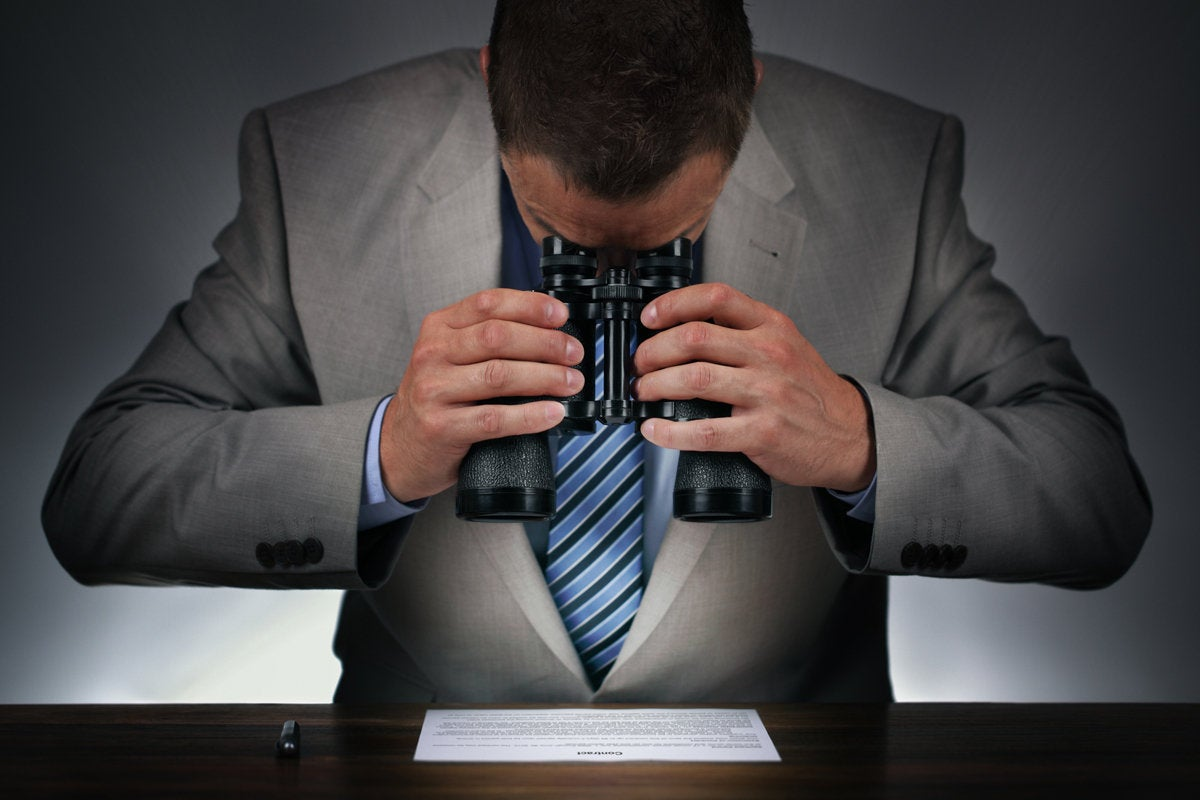 man with binoculars reading the fine print contract examine