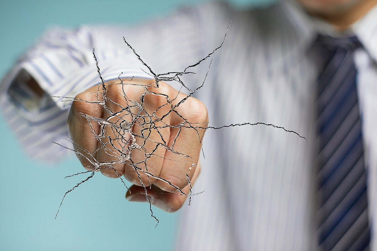 businessman's fist breaking through a barrier