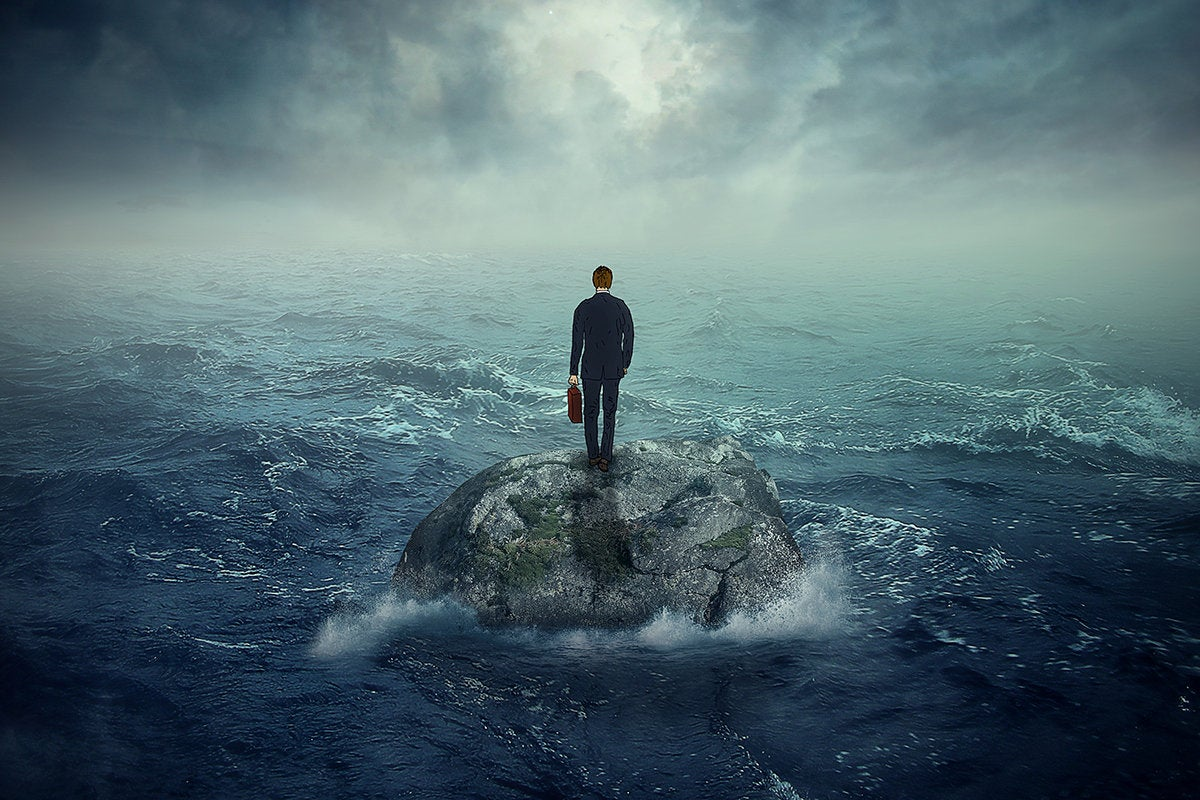 businessman on a rock in a stormy ocean
