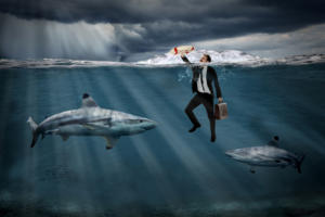 businessman swimming with sharks, reaching for a life preserver [disaster recovery]