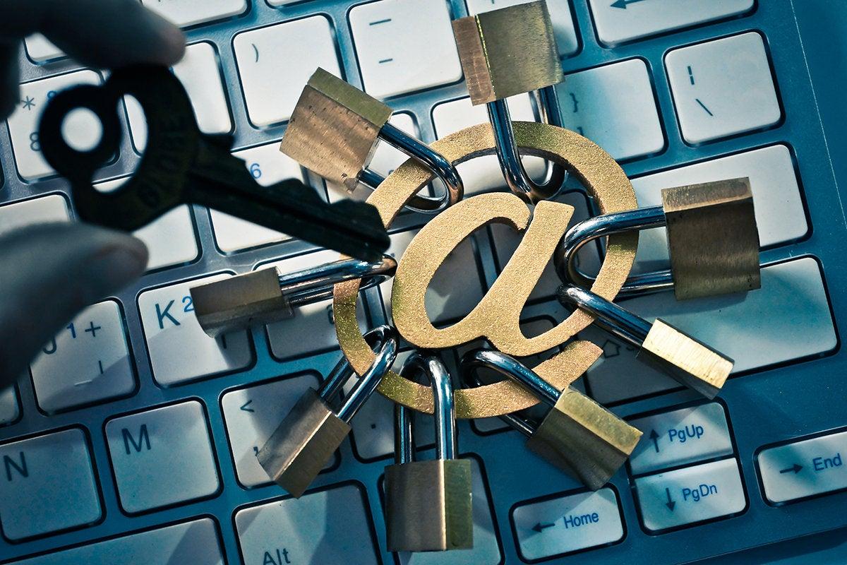 a hand holding a key moves toward an @ symbol with many locks