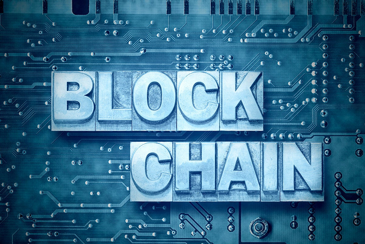 'blockchain' set in metal type against a circuit board