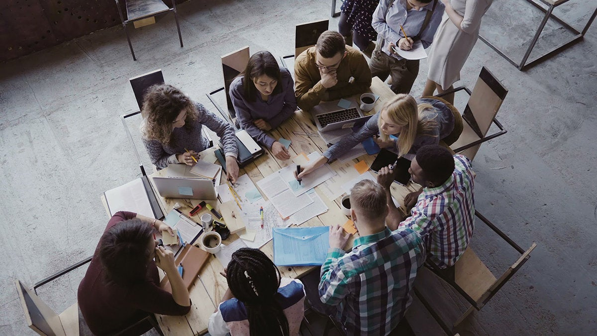 a team gathers around a table to work