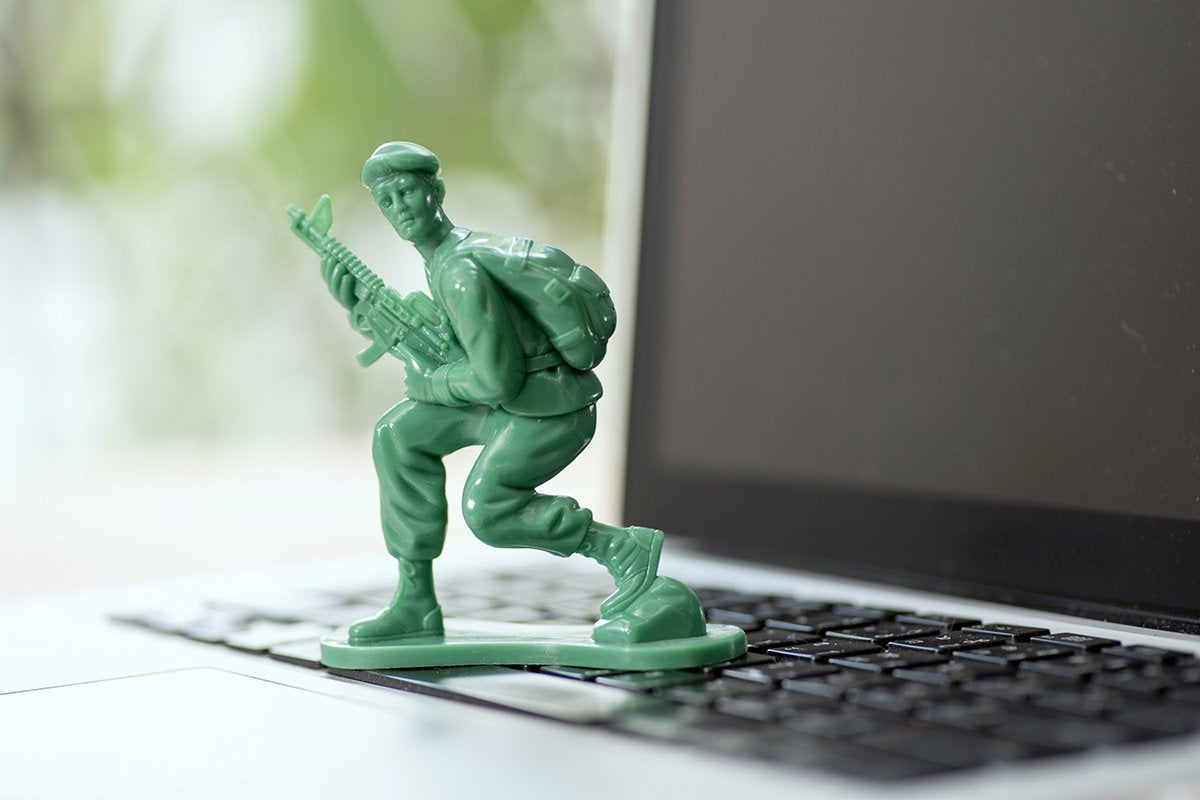 green army soldier on a laptop keyboard