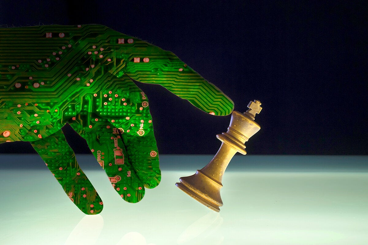 security threat - circuit board-hand knocking over a chess piece
