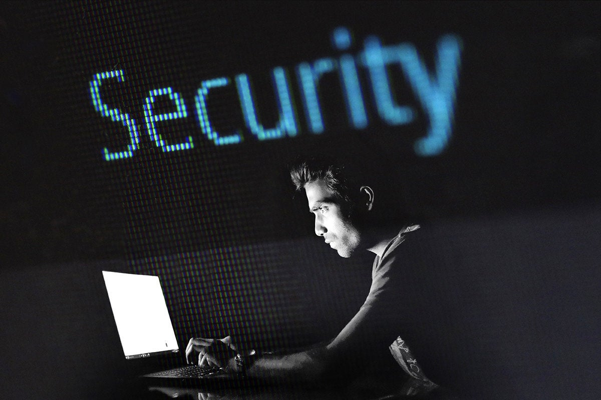young man using a laptop with a security display in the background