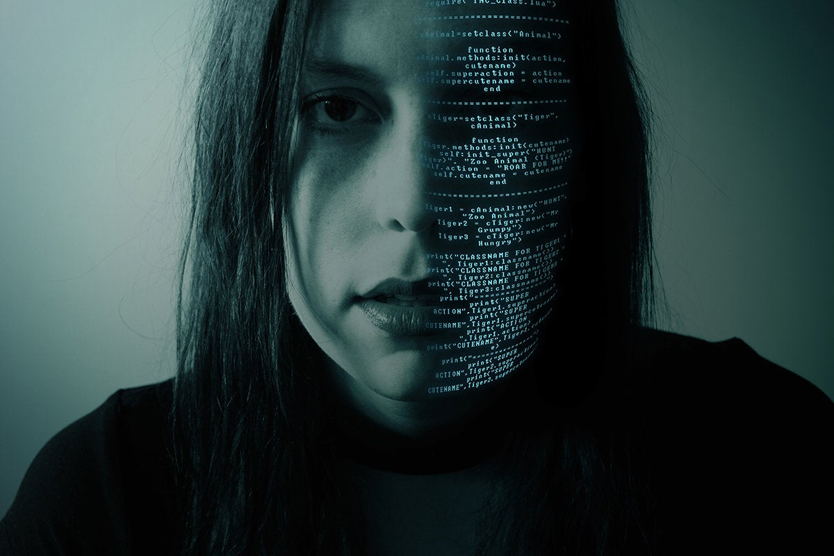 woman in darkness with half of her face in code