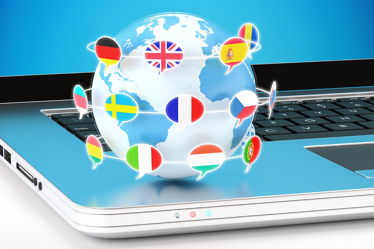 Globe with orbiting speech bubbles containing world flags, sitting on the edge of a laptop.