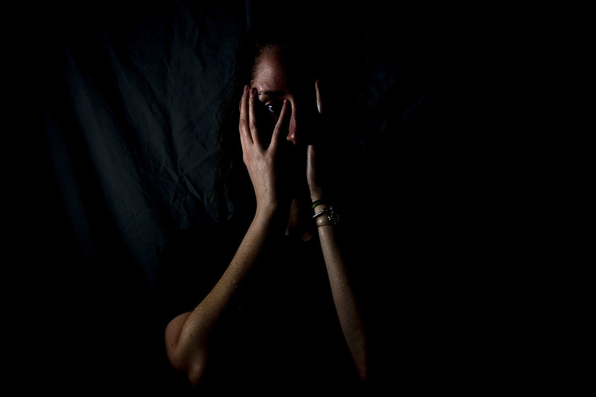 fearful woman covers her face with her hands / afraid / distressed