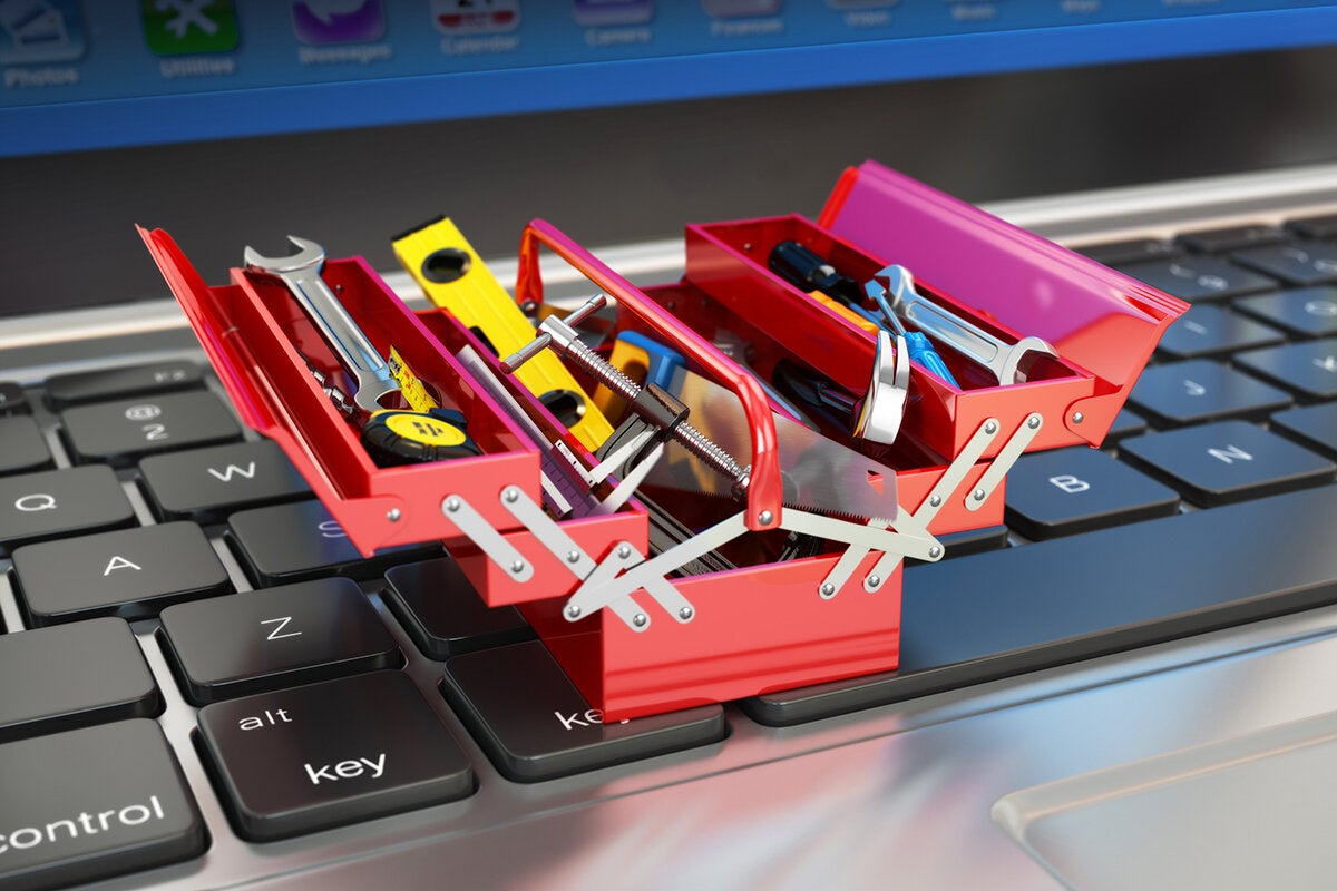 a miniature toolbox or toolkit on a laptop keyboard to build, develop or repair
