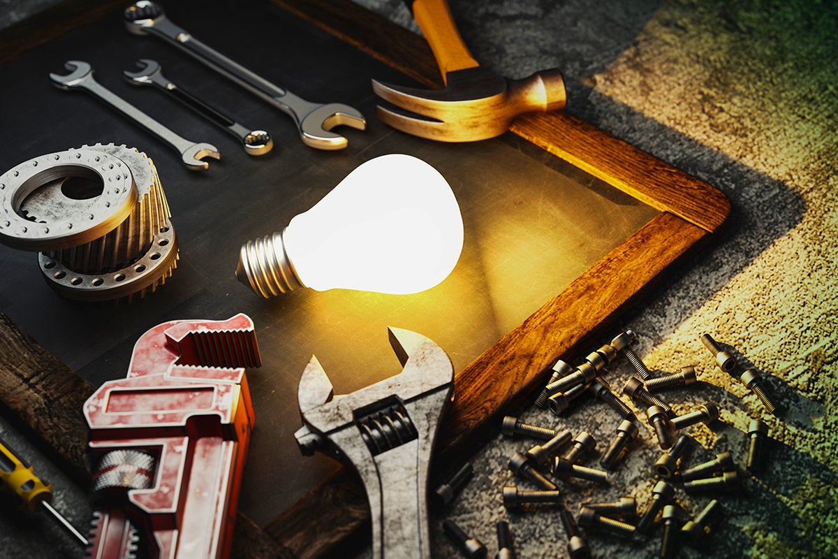 tools or toolkit surrounding a lightbulb on a chalkboard to build, develop or repair