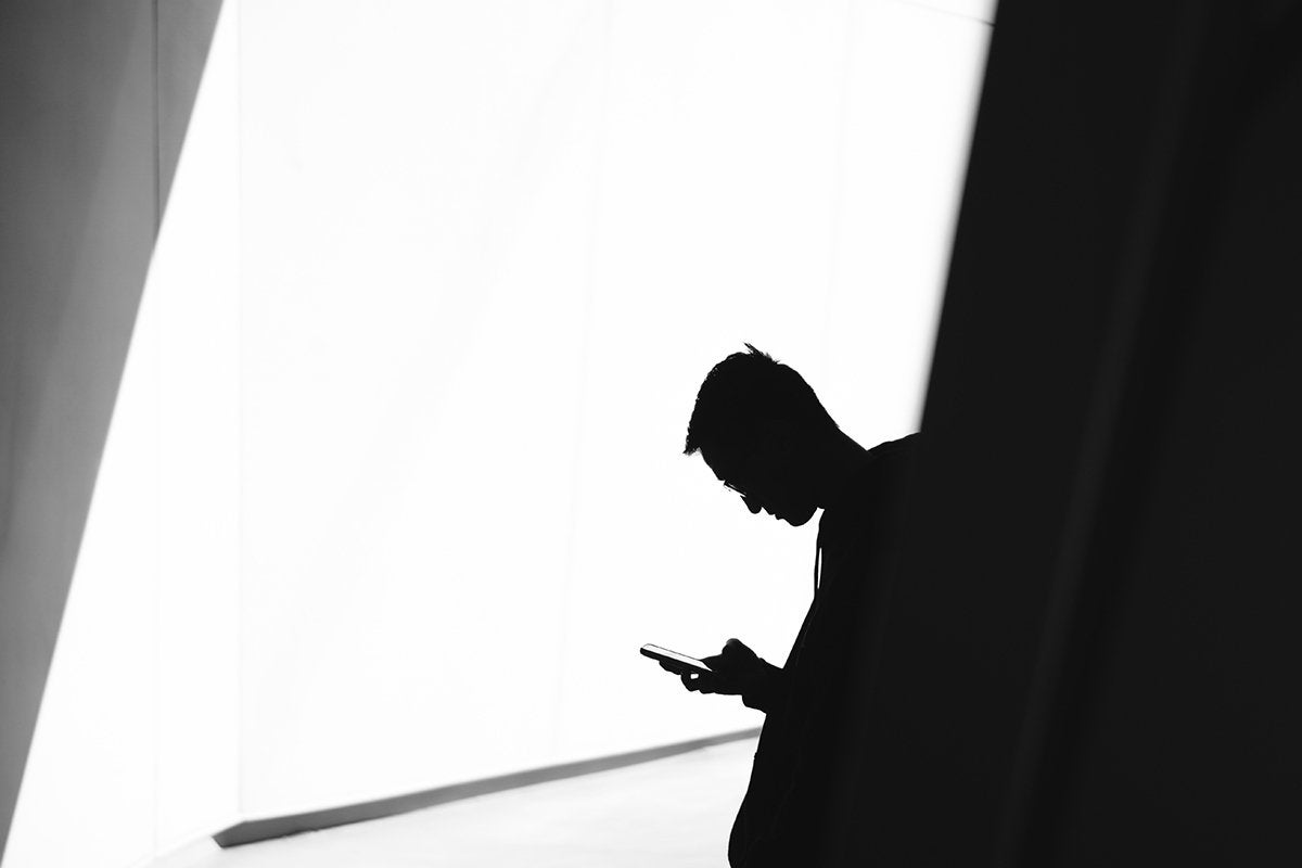 A man using a mobile phone in shadow against a bright wall