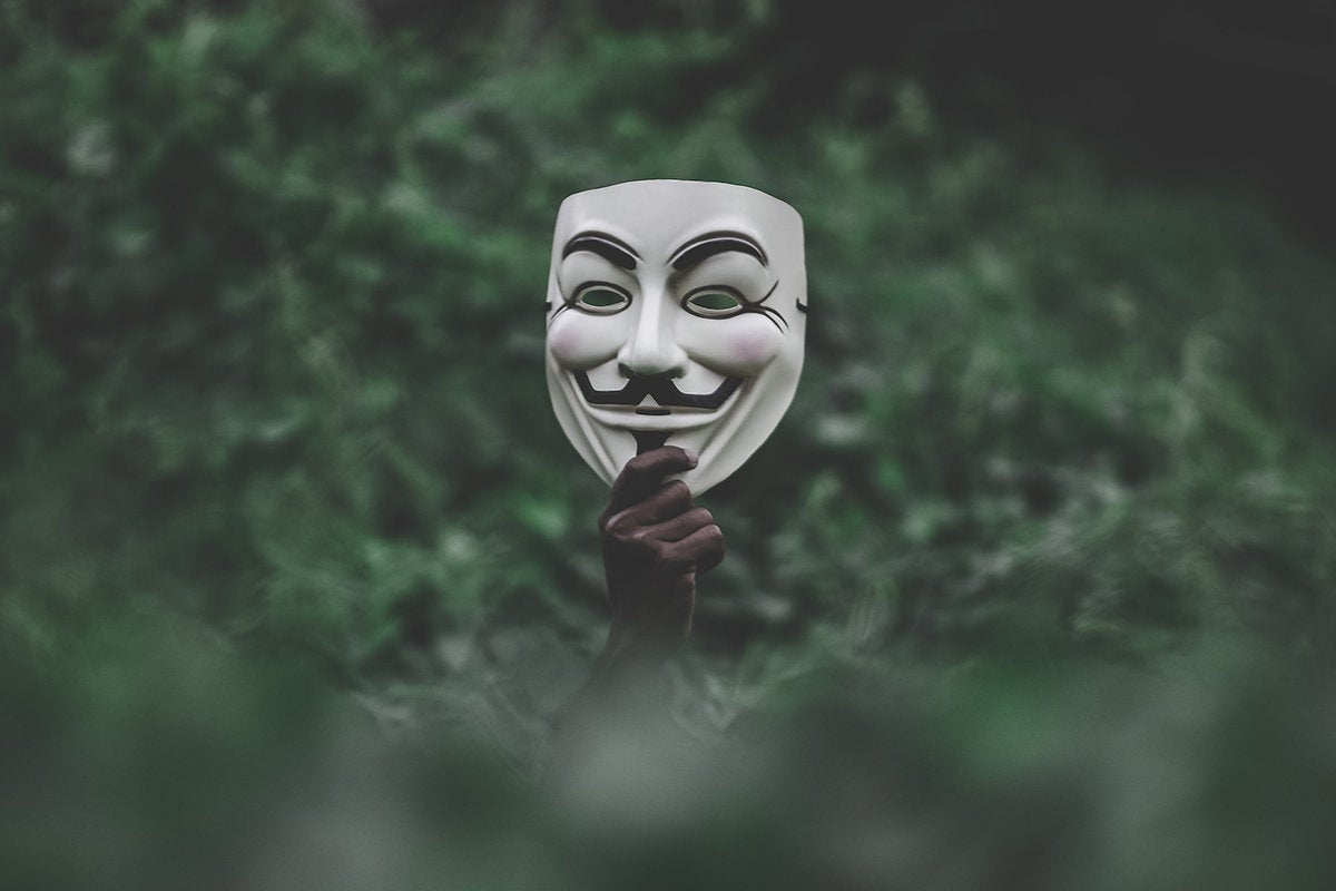 Guy Fawkes mask held aloft above the landscape / Anonymous / hacker / protest