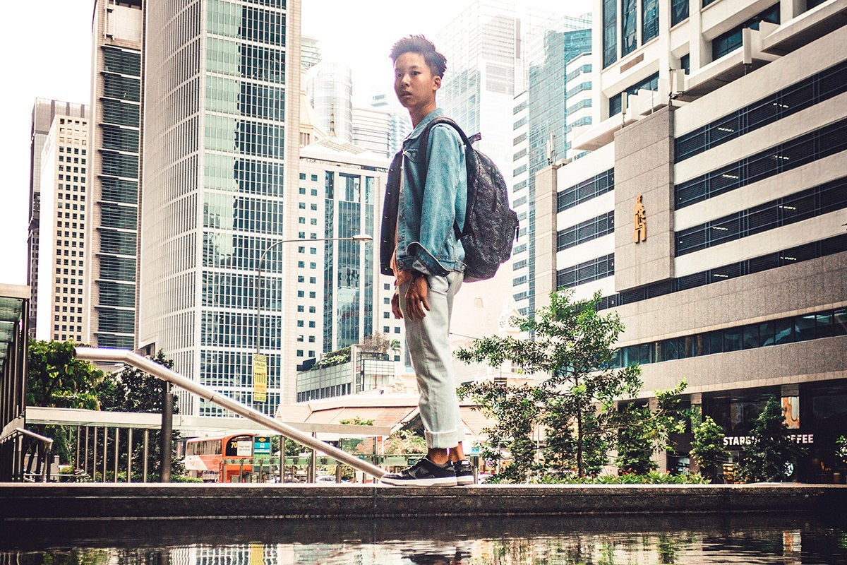 young man / student stands in a city street / next generation / Singapore