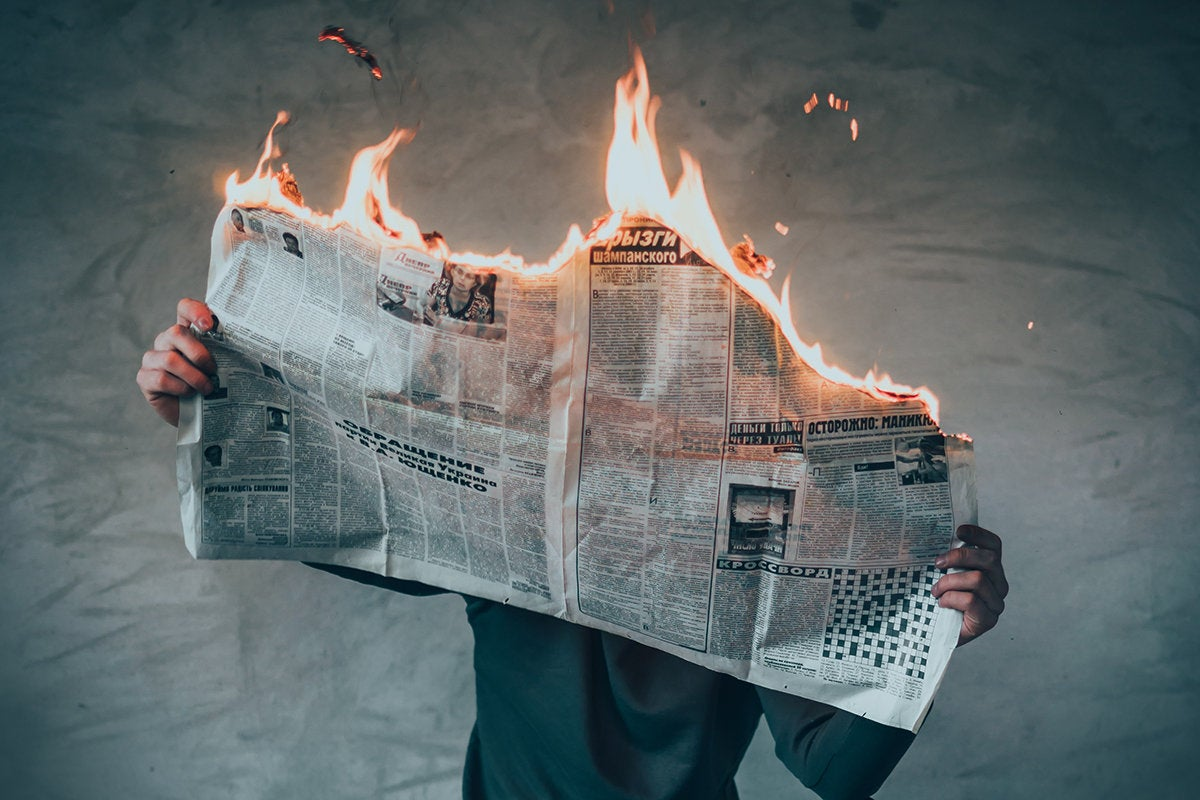 Bad News // A man reads a newspaper that is on fire.