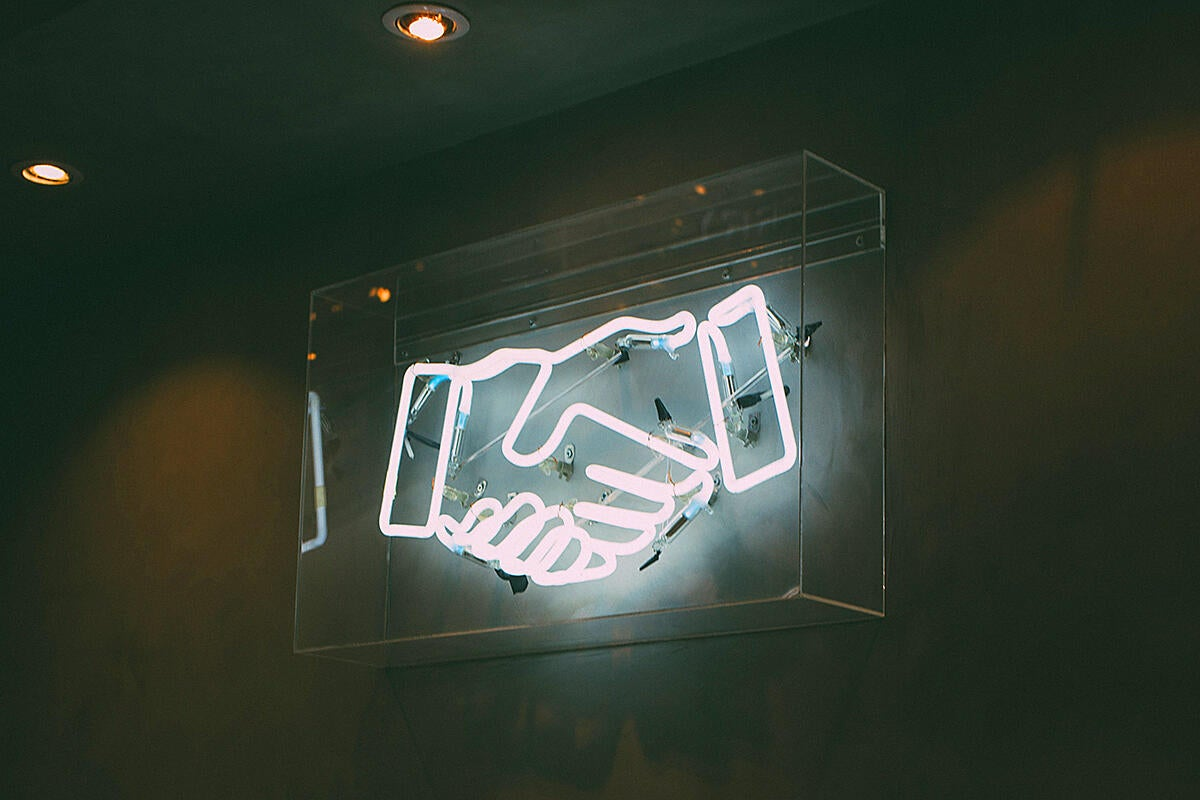 Neon sign > handshake / deal / agreement / partnership / team / merger