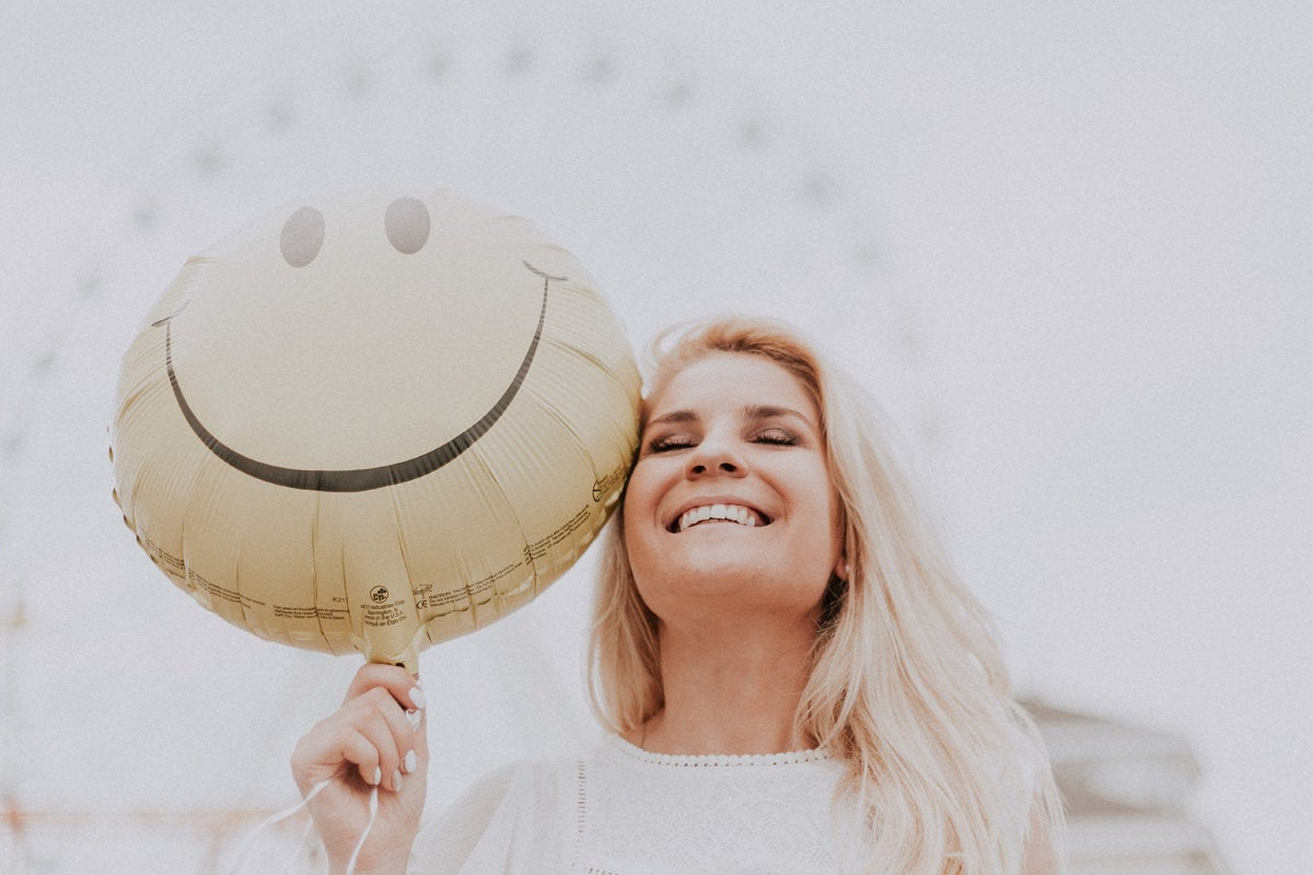 happy woman with smiley face balloon emoji content smiling laughing by pexels