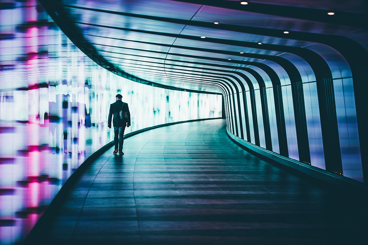 solidary individual walks alone through a tunnel of light
