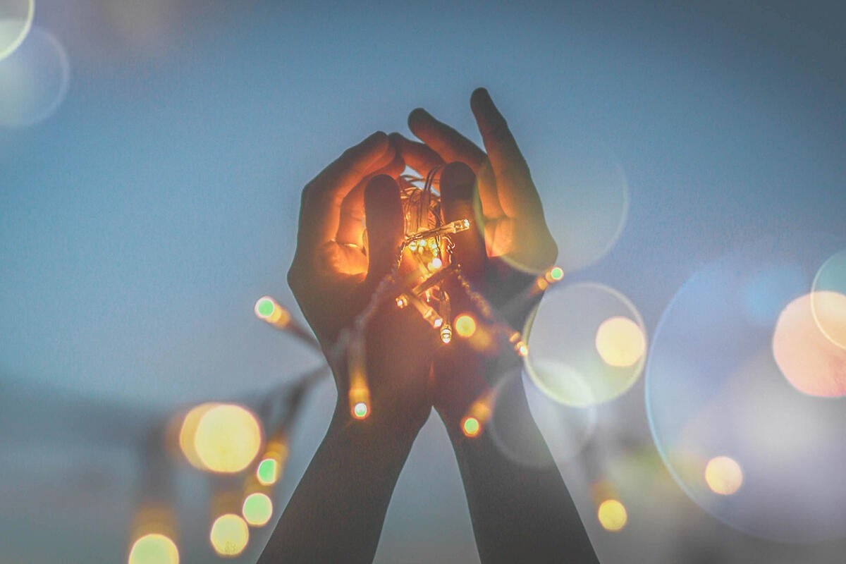 hands holding up a string of lights / ideas / innovation / brainstorming
