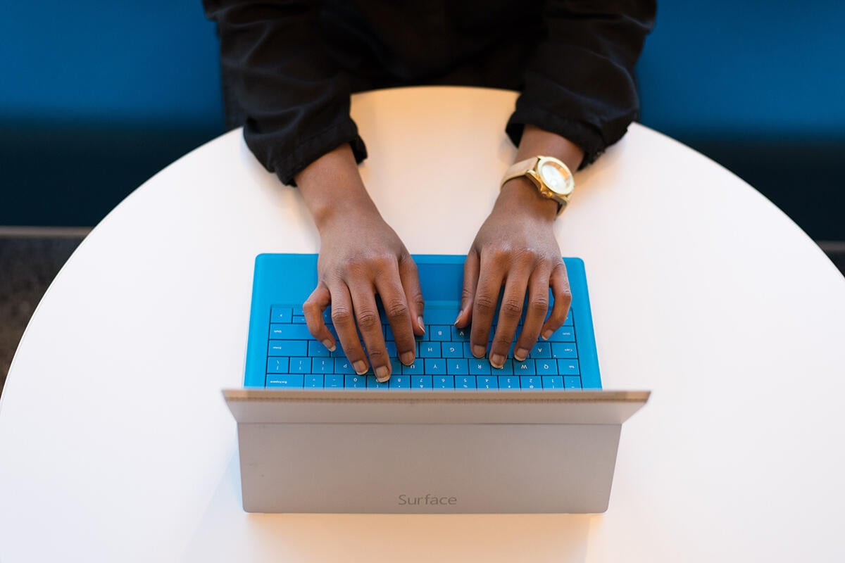 A woman uses the keyboard of a Microsoft Surface tablet.