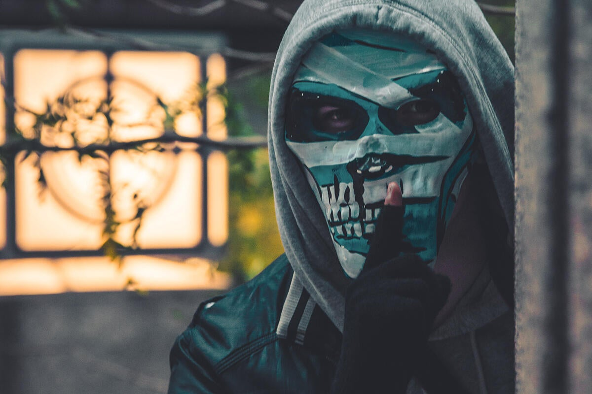 A hooded man in a halloween mask raises a finger to his lips to encourage silence.