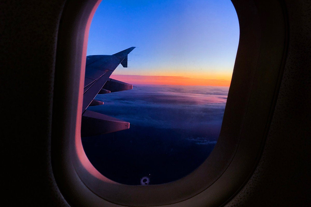 Passenger view of an airplane wing above the clouds. / travel / journey / transportation
