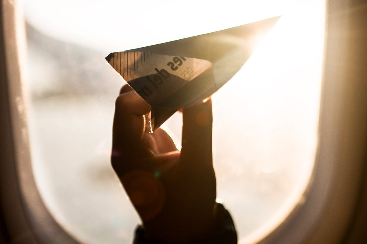 A passenger holds a paper airplane up to a window in flight. / travel / journey / transportation