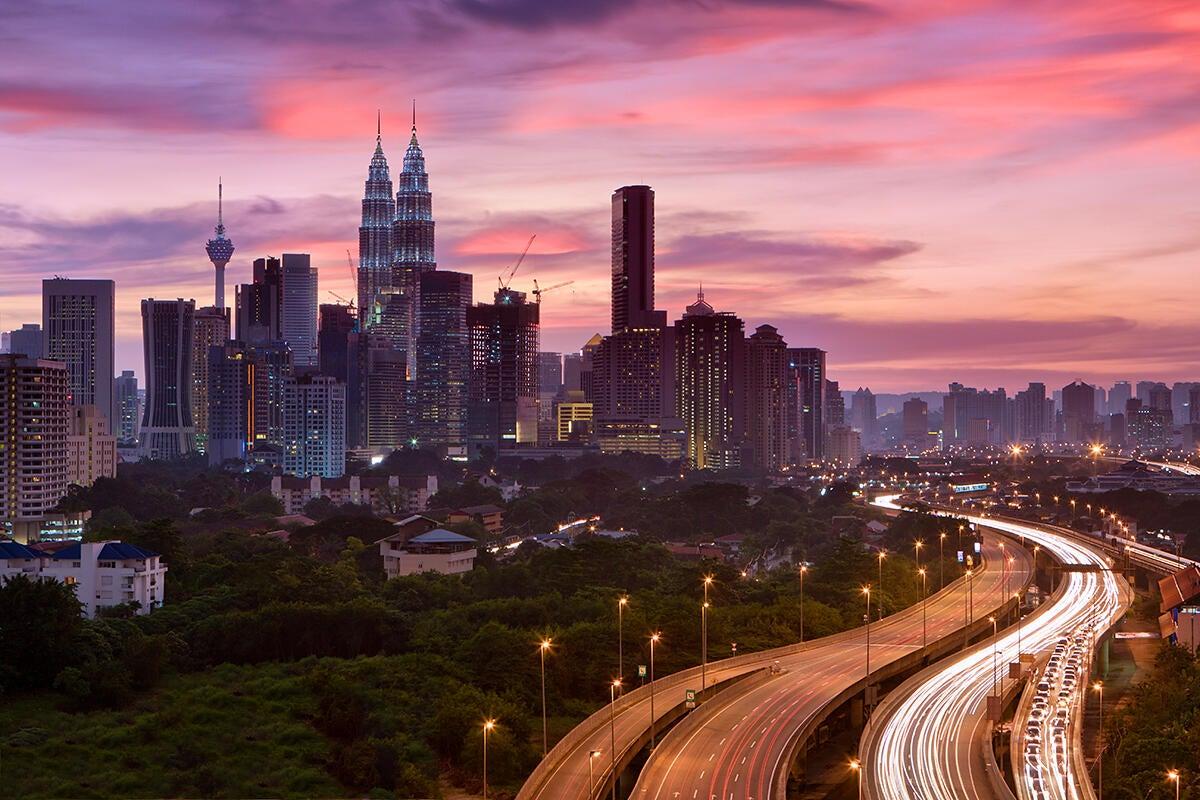 Kuala Lumpur skyline and traffic light trails at dusk, Malaysia, Southeast Asia