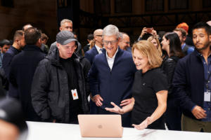 Apple Event [2018-10-30] > KAWS and Tim Cook check out the MacBook Air with an Apple team member.
