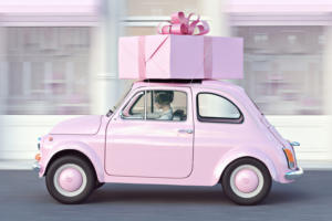 pink car with pink gift strapped to top retro euro car speed driving motion
