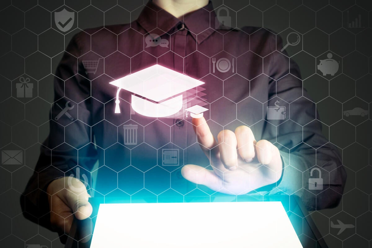 A woman holds a tablet and selects a graduation cap symbol from a virtual interface.
