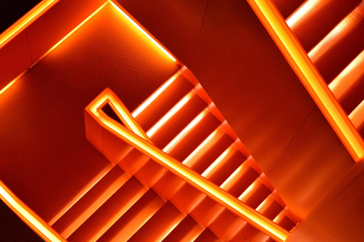 Aerial view of a glowing red staircase [movement/progress/descent/exit]