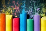 Seven (7) colorful chalks on blackboard / primary colors / secondary colors