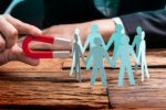 Recruiter attracts leads  >  Using a horseshoe magnet on a group of figurines.