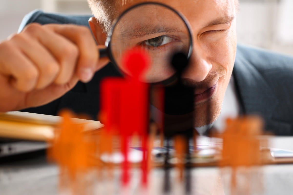 A man looks through a magnifying lens at a group of figurines.